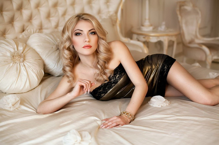 Exclusive escort in Istanbul chick Eva is lying on the bed wearing something shiny and gorgeous and her curls on the hair are maddening
