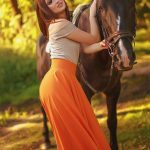 Eskortlar girl Alina is superb lover that is standing nearby the horse and poses us with the light charming smile